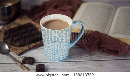 Cup Of Hot Chocolate With Spoon, Book And Chocolate Pieces. Cozy Composition