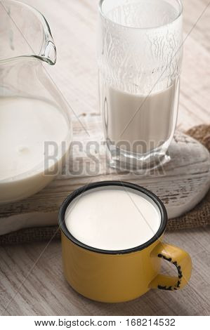 Glass and pitcher of kefir and cup on a white stand vertical