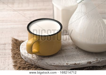 Glass pitcher yellow cup of kefir on the napkin and white stand horizontal