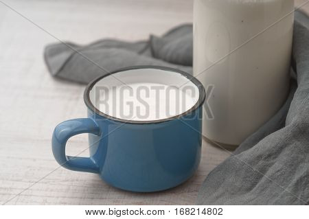 Cup with kefir and a bottle on a wooden table horizontal