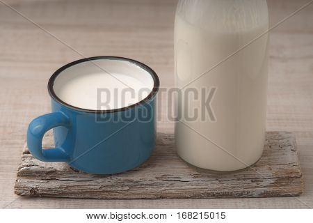 Cup with kefir and a bottle on a wooden stand horizontal