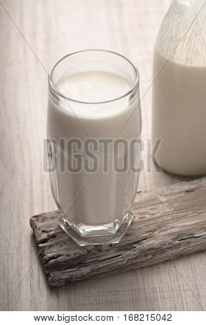 Glass with kefir and a bottle on a old stand vertical