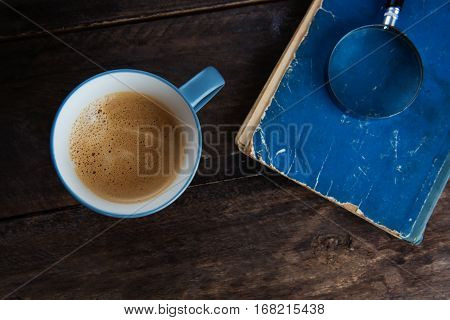A cup of coffee on the wooden background with the book