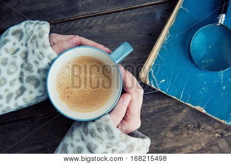 A cup of coffee in hand on a wooden background book and magnifier close