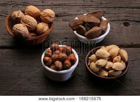 Group of different nuts and almonds over a wooden background.