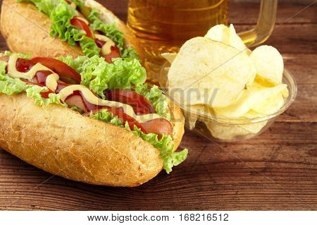 Hot Dogs With Glass Of Beer With Crisps On Wooden Board