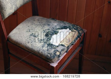 old wooden chair with a torn seat