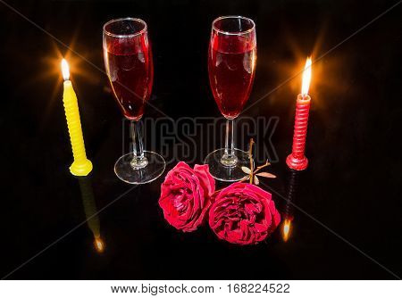 Romantic setup with burning candles red roses and red wine glasses in dark background.