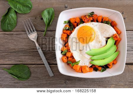 Breakfast Nutrient Bowl With Sweet Potato, Egg, Avocado And Spinach Above Scene On Rustic Wood