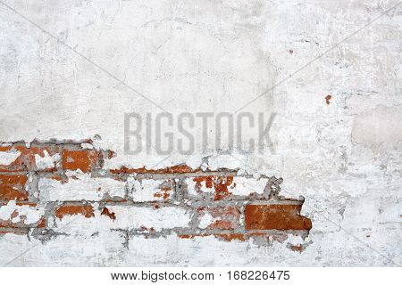 Red brick wall with peeled plaster. Shabby building facade with cracked plaster.
