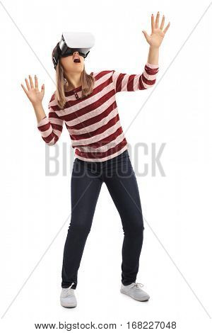 Full length portrait of a girl experiencing virtual reality through a VR headset isolated on white background