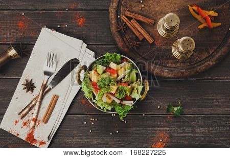 Vegan and vegetarian dish, fresh vegetable salad in copper bowl. Indian restaurant, lettuce and fruits mix with herbs, healthy meal, top view on wood background. Eastern local cuisine food.