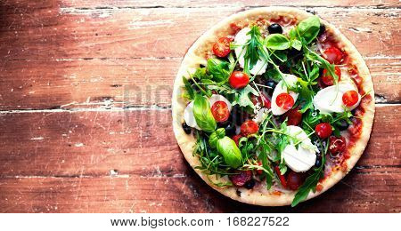 Hot pizza with meat basil and mozarella cheese on a dark background top view. Pizza on the rustic wooden table with copy space