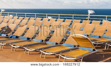 many empty chairs in relaxation area on stern of cruise liner