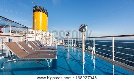upper deck of cruise liner with empty sunbathing chairs in summer morbning