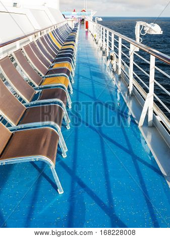 row of empty sunbathing chairs on deck of cruise liner