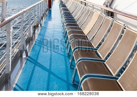 row of sunbathing chairs on deck of cruise liner