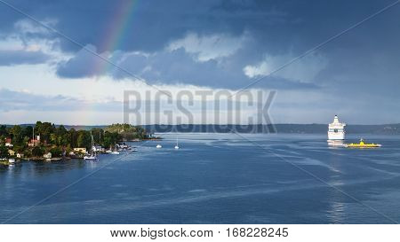 panorama with white cruise liner village on the seacoast and dark blue rainy clouds with rainbow over Baltic Sea in sunny autumn day Sweden