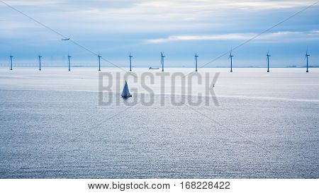 Travel to Denmark - airplane and ships near offshore wind farm Middelgrunden in Oresund near Copenhagen city in Baltic Sea in blue autumn morning