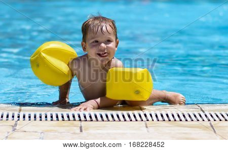 Happy Toddler swimming in the pool. Adorable cute baby boy with swimming water wings at the pool. Summertime holidays