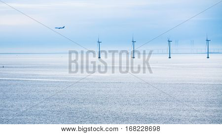 Travel to Denmark - view of airplane bridge and offshore wind farm Middelgrunden in Oresund near Copenhagen city in Baltic Sea in blue autumn morning
