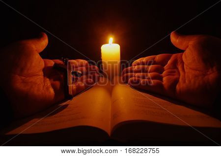Burning candle open Bible and prayer hands in the darkness.