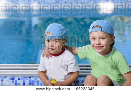 Two adorable sibling kids hugging and having fun outdoors. Cute brothers playing together on sunny warm summer day. Brother love. Happy boys smiling on a sunny day by the pool. Brothers portrait