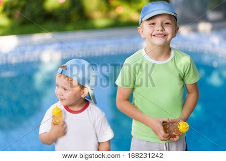 Sunny warm summer day. Brother love. Happy boys smiling on a sunny day by the pool. Brothers portrait