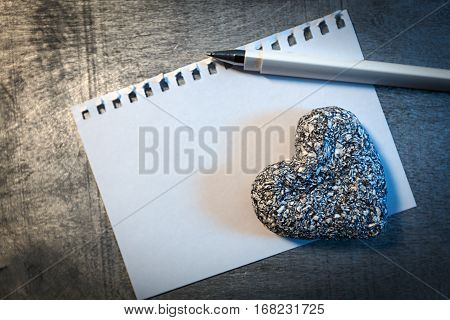 Love letter template on paper with pen and stone heart on wooden rustic desk horizontal top view