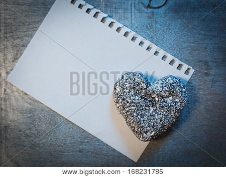 Love letter template on paper and stone heart on wooden rustic desk horizontal top view