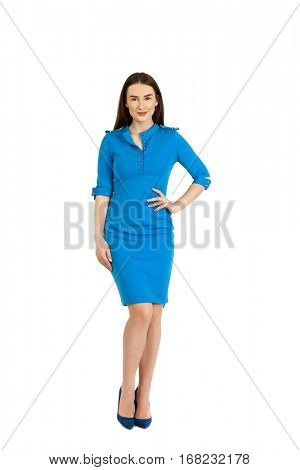 Full body slim woman in blue dress standing in studio, isolated on white