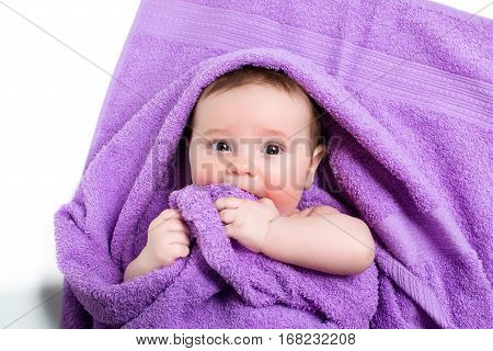 Newborn baby lying down and smiling in a purple towel.