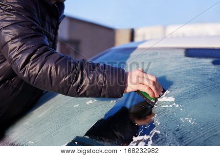 Man scraping ice from the windshield of a car covered wit hoarfrost poster
