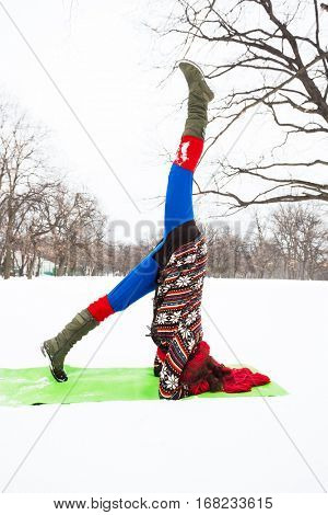 young woman doing yoga in winter snow covered park