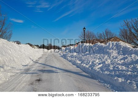 Plowed road in a North American neighborhood after a big storm.