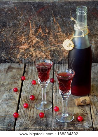 Sweet cranberry alcohol drink liqueur in two glasses and bottle on wooden background. Selective focus