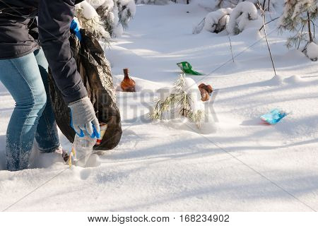Girl Collects Garbage From The Snow In The Forest