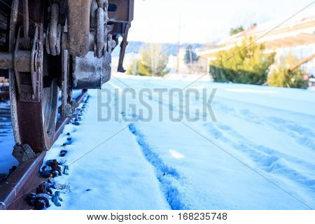 Train closeup on covered with snow railroad tracks