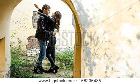 Beautiful young man and woman hugging, standing in the arch of the old dilapidated building. Place for text