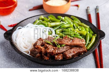 Fried Spicy Beef With Sesame Seeds, Green Beans And Rice Noodles. Dinner In The Asian Style. Selecti