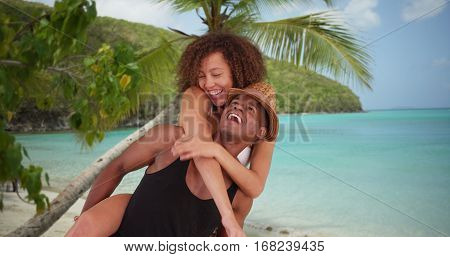 African American Millennial Couple Give Each Other Piggy Back Rides By The Beach