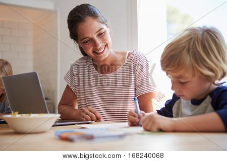 Mother watching son colouring at the kitchen table