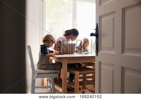 Mum and two kids working in kitchen, close up from doorway