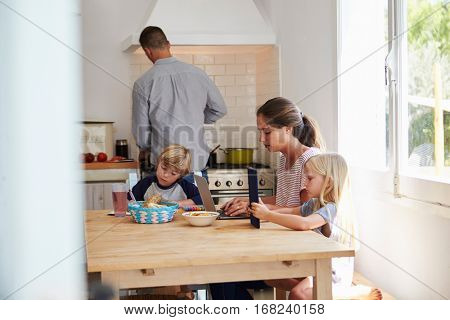 Kids and mum at table, dad cooking, three quarter length