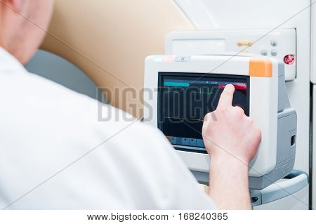 Close Up Doctor Adjusts Electrocardiograph In Computed Tomography Room. Selective Focus