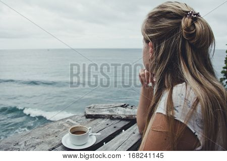 Girl relaxes, drinking coffee and enjoying the view of the ocean, Bali