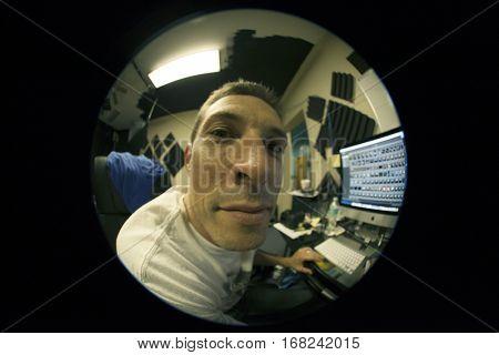 Overworked man on computer shot through 180 degree fisheye lens