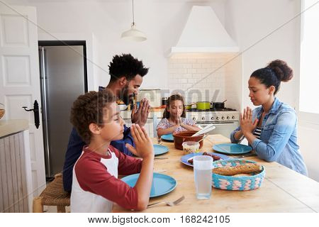 Family saying grace at the kitchen table before their meal