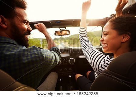 Happy couple driving in their car with arms in the air