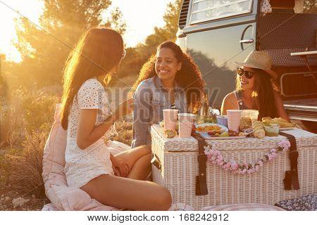 Three female friends enjoying a picnic by their camper van